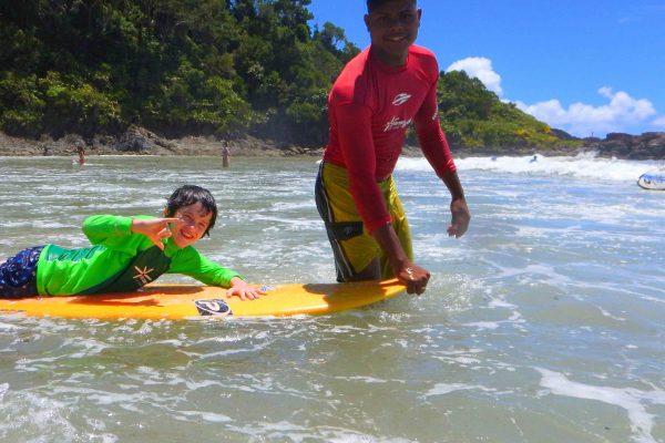 instrutor de surf com criança em longboard